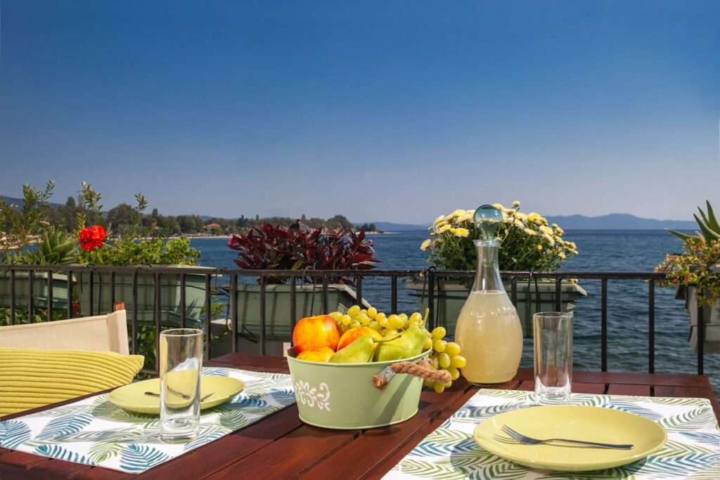 table by the sea with a basket of fruits