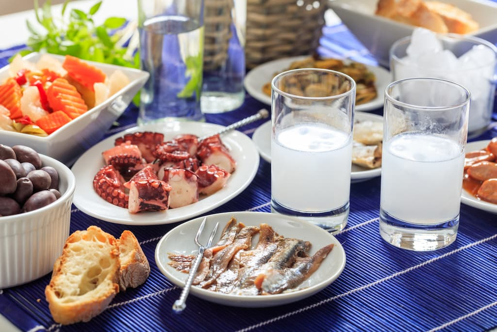 Table with tsipouro and greek traditional dishes